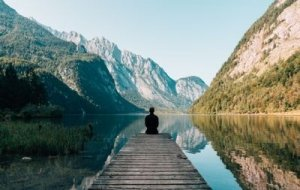 Man sitting on pier on lake with mountains in the background: contemplating - Awakening Alchemy