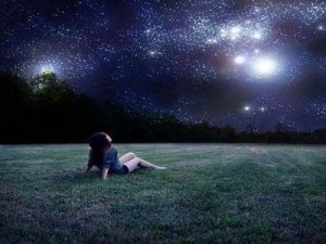 Girl Sits on Grass and Gazes at the Stars at Night - Awakening Alchemy