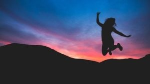 Silhouetted Figure Jumps For Joy against a Gorgeous Sunset - Awakening Alchemy