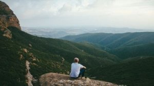 Man Sits on a Rock Hiugh in the Mountains Meditating - Awakening Alchemty