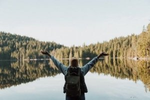 Person With Hands Raised at Edge of Lake Praising Nature - Awakening Alchemy