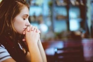 A Young Woman Praying in Church - Awakening Alchemy