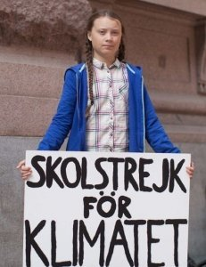 Schoolgirl Climate Activist Greta Thunberg with sign announcing she is striking for the Climate - Awakening Alchemy