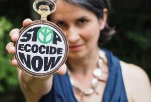 Stop Ecocide Founder Polly Higgins Holding a Stop Ecocide Now Logo - Awakening alchemy