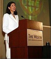 Debra Poneman Speaking at a Lecturn: All White Suit - Awakening Alchemy